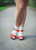 与白色袜子的红色凉鞋在五十年代样式的女孩腿 免版税库存图片