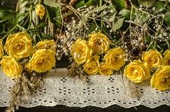 与白色被绣的边界谎言黄色玫瑰的黑胶合板 图库摄影