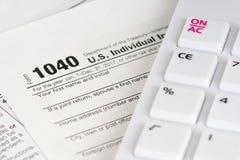 1040与白色计算器的报税表 图库摄影