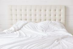与白色软的鸭绒垫子的空的床有没人的 宽敞卧室和舒适的床您的放松和休息的供时间概念住宿 免版税库存图片