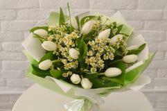 与白色郁金香和camomiles的美丽的花束 免版税库存照片