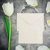 与白色郁金香的花卉构成和与卡片的纸信封在黑暗的背景 平的位置,顶视图 花卉样式backgroun 免版税图库摄影