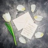 与白色郁金香的花卉构成和在黑暗的背景的纸信封 平的位置,顶视图 花卉样式背景 免版税库存照片