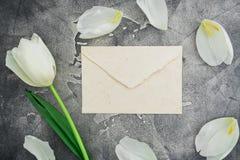 与白色郁金香的花卉构成和在黑暗的背景的纸信封 平的位置,顶视图 空白背景概念性绿色查出的梨 库存图片