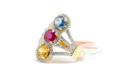 与白色金刚石和金戒指的红色,黄色和蓝色金刚石 图库摄影