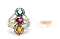 与白色金刚石和金戒指的红色,黄色和蓝色金刚石 免版税库存照片