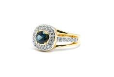 与白色金刚石和金戒指的蓝色青玉 免版税库存照片