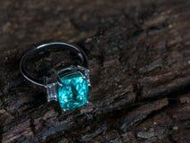 与白色金刚石的特写镜头绿色宝石圆环在老木backgrou 图库摄影