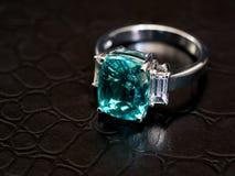 与白色金刚石的特写镜头绿色宝石圆环 免版税图库摄影