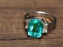 与白色金刚石的特写镜头绿色宝石圆环 免版税库存照片