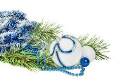 与白色闪烁被隔绝的圣诞树分支和蓝色球 免版税库存照片