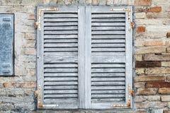 与白色闭合的木快门的老窗口 库存照片