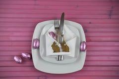 与白色陶器的桃红色复活节桌餐位餐具和发光的鸡蛋用木小兔塑造装饰 库存图片