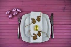 与白色陶器的桃红色复活节桌餐位餐具和发光的鸡蛋用木小兔塑造装饰 库存照片