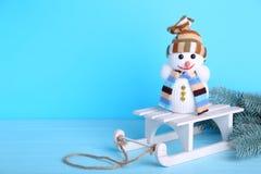 与白色雪橇的小雪人在蓝色背景 免版税库存图片