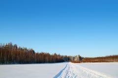与白色雪的森林、领域和滑雪轨道冬日 免版税图库摄影