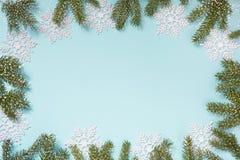 与白色雪花和分支的圣诞节创造性的边界在蓝色背景 平的位置 复制空间 拉长的雪 免版税库存照片