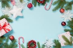 与白色雪花和分支的圣诞节创造性的边界在蓝色舱内甲板位置 顶视图 复制空间 拉长的雪 免版税库存照片
