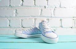 与白色鞋带特写镜头的Keds在木flloor对一个白色砖墙 免版税库存图片