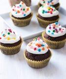 与白色结冰的巧克力杯形蛋糕 免版税库存照片