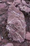 与白色水晶的红色水成岩表面上 图库摄影