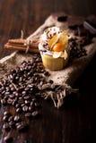 与白色黄油奶油的巧克力杯形蛋糕,装饰用在黑暗的木背景的酸浆 装饰用stic的桂香 库存照片