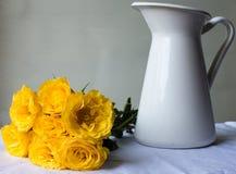 与白色水罐的黄色玫瑰 免版税库存图片