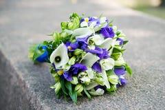 与白色水芋属和紫罗兰色花的婚礼花束 免版税库存图片