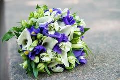 与白色水芋属和紫罗兰色花的婚礼花束 免版税图库摄影