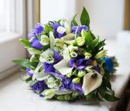 与白色水芋属和紫罗兰色花的婚礼花束 免版税库存照片