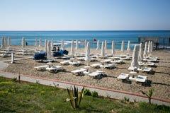 与白色sunbeds和伞的美丽的海滩 图库摄影