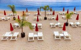 与白色sunbeds和红色伞的空的海滩 库存图片