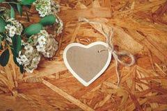 与白花和绿色叶子的小心脏卡片在纹理木背景 免版税库存图片