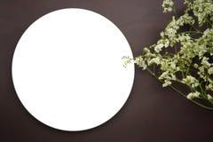 与白花的白色盘在棕色皮革背景 免版税库存照片
