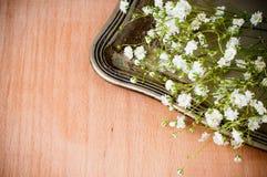 与白花的背景,古色古香的盘 免版税库存照片