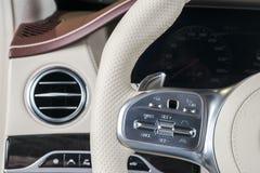 与白革方向盘的豪华现代汽车内部有媒介的给控制按钮,航海屏幕多媒体系统打电话 免版税库存照片
