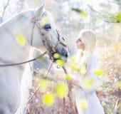 与白马的白肤金发的若虫 免版税库存图片