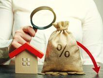 与百分之的金钱袋子,在箭头和微型房子下 低息率的概念在抵押贷款或租务的 ?treadled 库存图片
