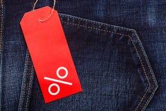 与百分号的红色标签在牛仔布 免版税库存照片