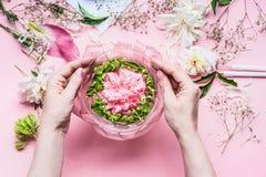 与百合和其他花,玻璃花瓶的桃红色卖花人工作区用水 做欢乐花的布置的女性手 免版税库存照片