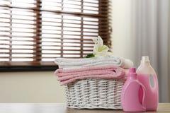 与百合的在户内桌上的清洁毛巾在篮子和洗涤剂 库存图片
