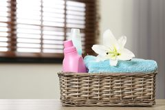 与百合的在篮子的清洁毛巾和洗涤剂在户内桌上 r 库存图片