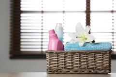 与百合的在篮子的清洁毛巾和洗涤剂在桌上 免版税库存图片