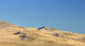 与的冬天风景用黄色干草和第一雪盖的光滑的小山在深蓝天空下 免版税库存照片