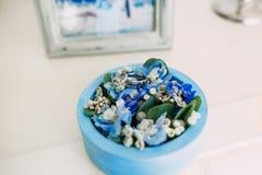 与的婚戒在一个蓝色圆的箱子的宝石有蓝色花的 附庸风雅 软绵绵地集中 免版税库存图片