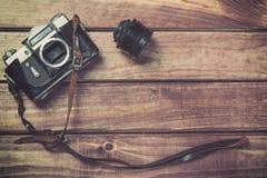 与皮带的老影片在木背景的照相机和透镜 与自由空间的葡萄酒被定调子的和顶视图 图库摄影