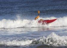 有皮船的人在风大浪急的海面 库存照片
