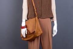 与皮革棕色提包的时装模特 免版税库存照片