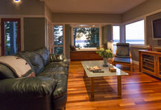 与皮革长沙发、玻璃咖啡桌、靠窗座位和窗口的当代高级家庭客厅内部有水视图 免版税库存图片