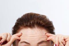 与皱痕的宏观妇女面孔在前额 胶原和面孔射入概念 更年期 播种的图象 复制空间 免版税库存图片